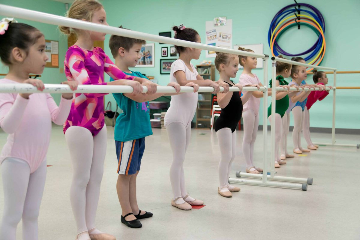 Group of young children in leotards and dance attire standing at the barre for ballet class