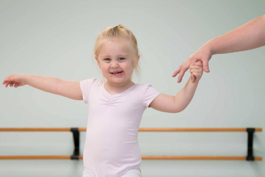 toddler in a pink leotard taking part in a mommy & me dance class