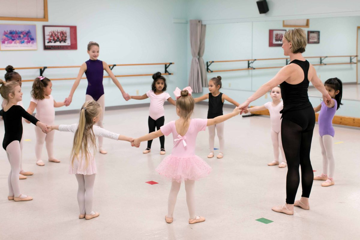 10 young female dance students standing in a circle in the studio with their teacher before starting preschool dance class