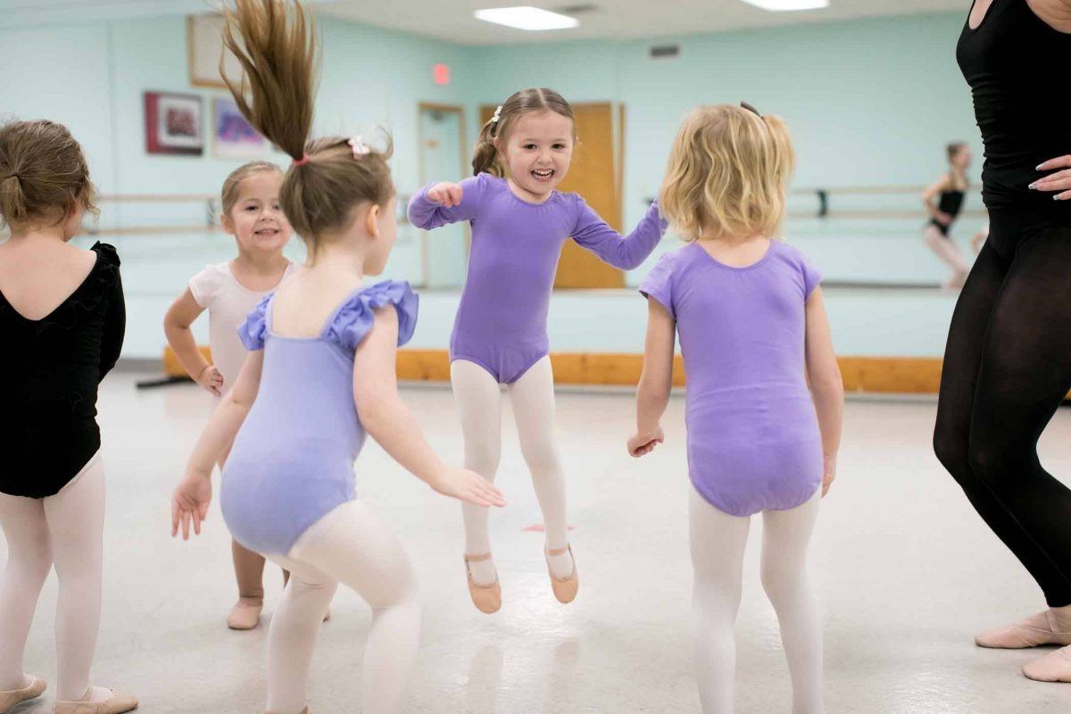 five female children in dance leotards, tights, and ballet slippers jumping and moving in preschool dance class