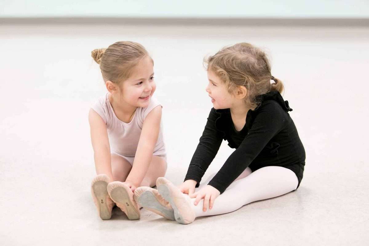 two caucasian female children in ballet leotards and tights smiling and stretching before prechool dance class