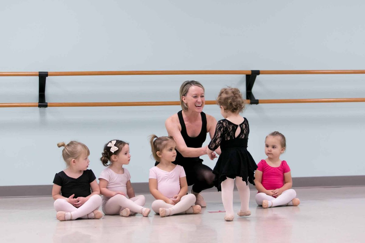 5 toddlers sitting and talking to their teacher in a ballet studio before preschool dance class